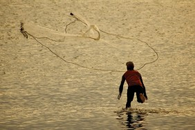 A fisherman net casting on New Caledonia's lagoon.